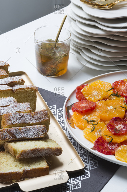 Sliced pound cake served with fresh citrus pieces and sauce