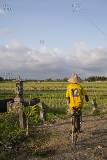 Rear view of biker wearing traditional conical Asian hat and sports jersey