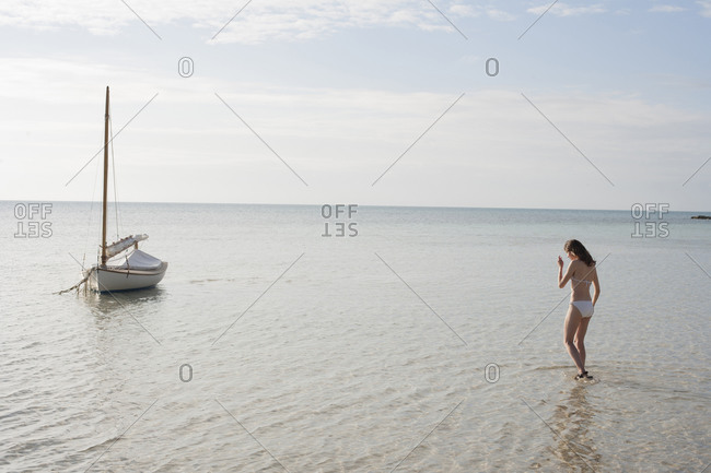 Young woman walking in shallow water at the beach