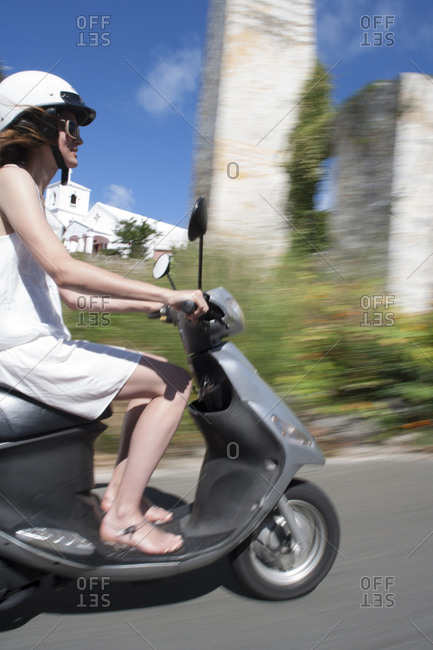 Side view of young woman driving a scooter