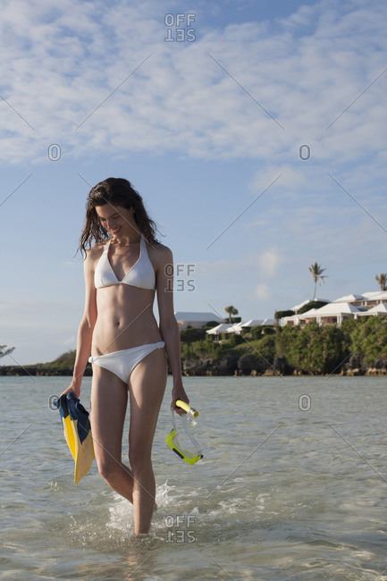 Young woman walking in shallow water and carrying snorkeling equipments