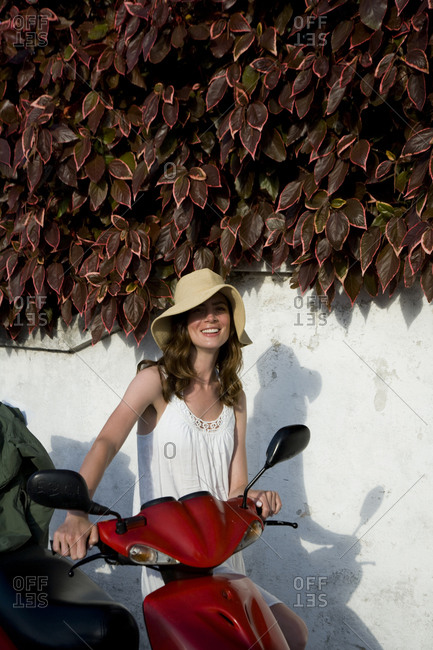 Portrait of young woman standing with a scooter