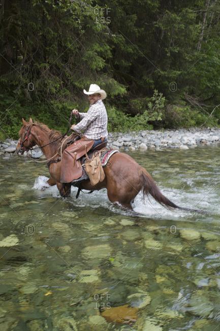 Cowboy crossing a river on horseback