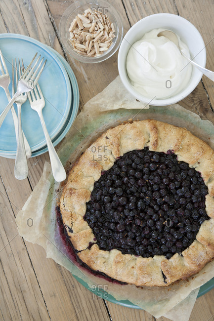 Blueberry pie with cream and chopped, roasted almonds