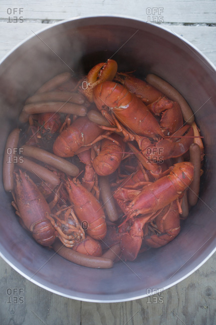 Pot of steaming sausages and lobsters