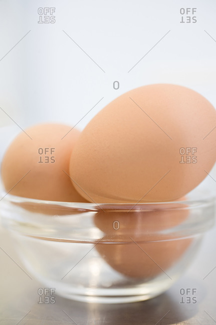 Close-up of three eggs in a glass bowl