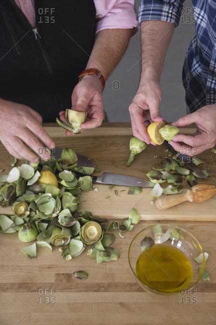 Two man preparing artichokes