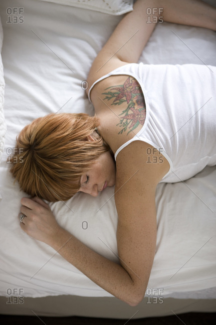 Young woman sleeping on bed, elevated view