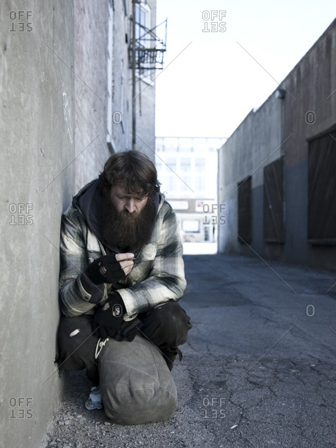 Homeless man with sack by roadside