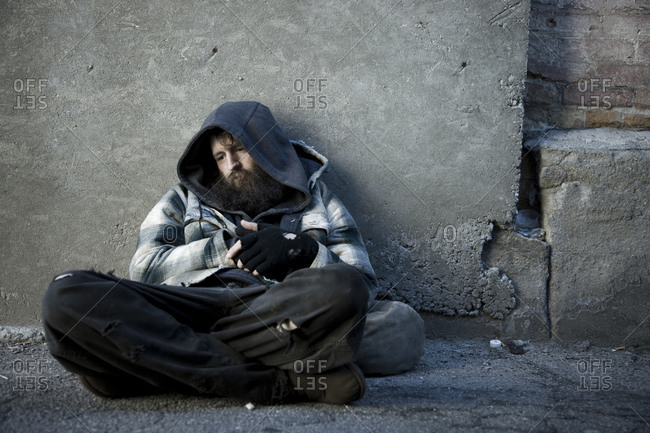 Homeless man sitting on sidewalk