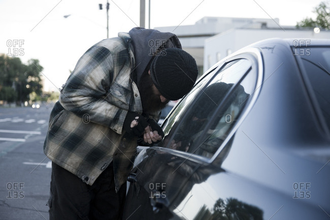 Homeless man breaking into car, side view