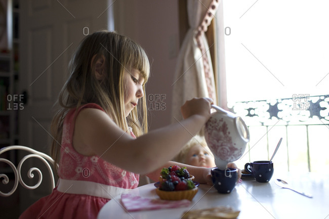 Girl (2-3) pouring tea in cup