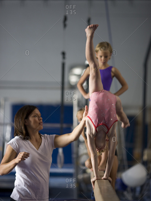 Instructor helping gymnasts (6-9) to perform handstand on beam