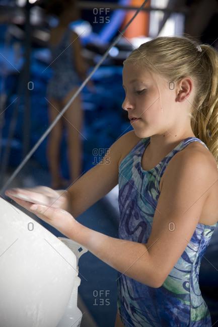 girl (10-11) in gym applying talcum powder to hands