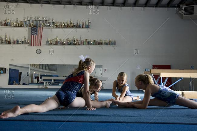 Girls (8-11) stretching in gym