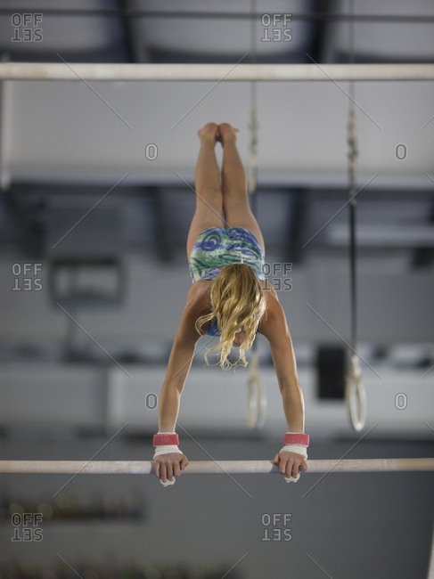 girl (10-11) exercising on pole in gym