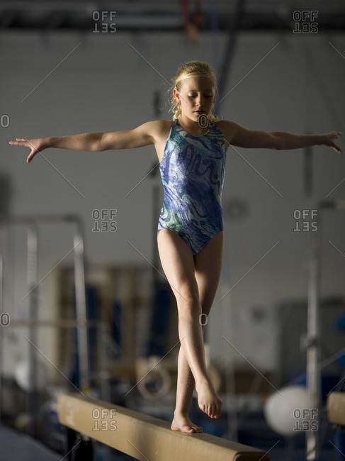 girl (10-11) exercising on balance beam
