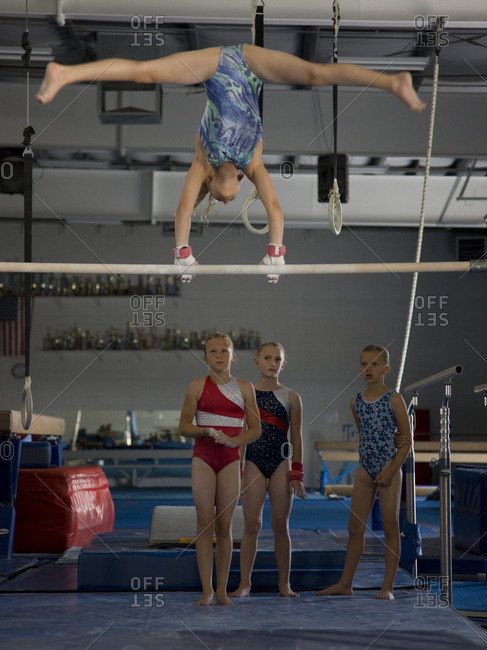 girls (10-11) in gym watching friend exercising on pole