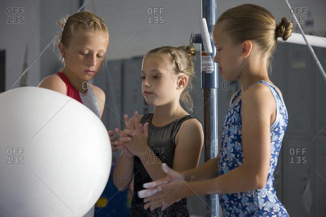 girls (8-11) in gym applying talcum powder to hands