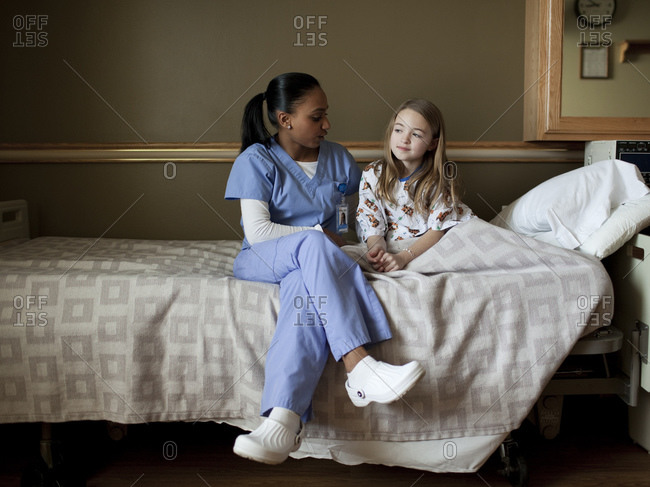 Young nurse embracing girl (8-9)