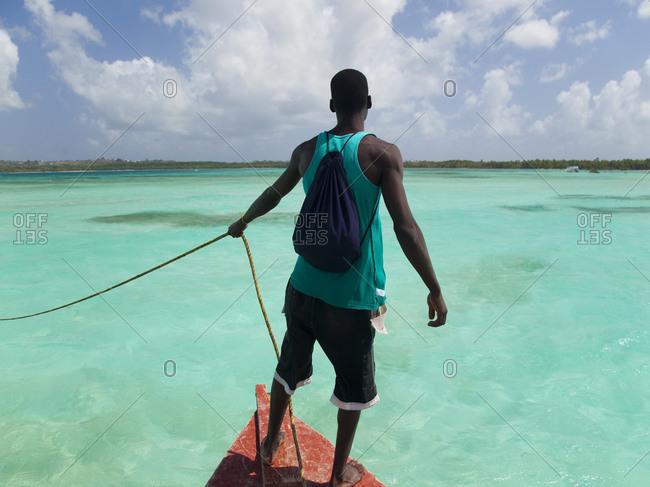 Grenada, Caribbean Sea, Man on top of boat looking at view