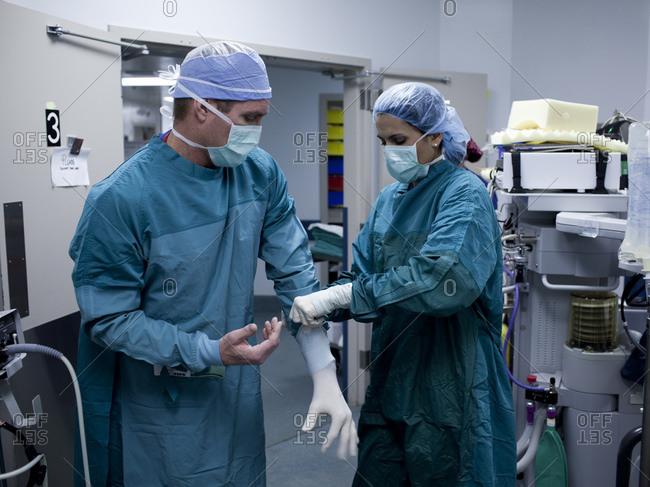 Surgeon and nurse preparing for surgery