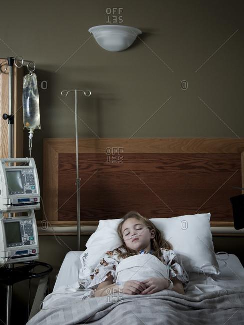 Girl (8-9) sleeping on hospital bed