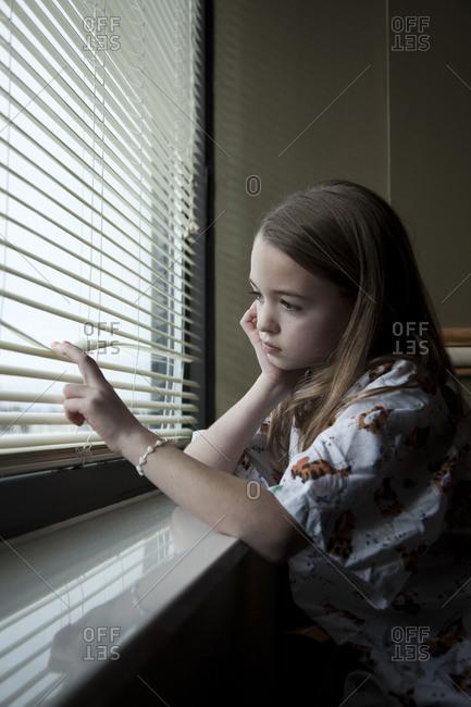 Girl (8-9) looking through window