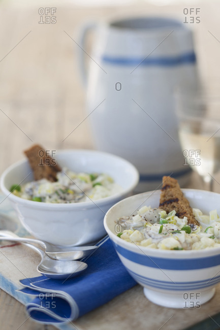 Two bowls of New England clam chowder with toast
