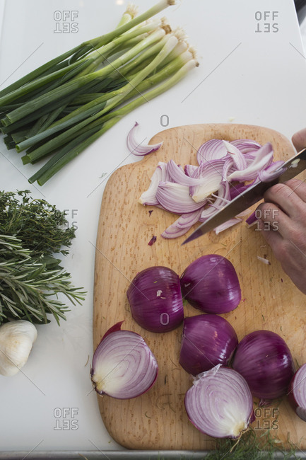 Knife cutting raw red onion and bundle of scallions on countertop