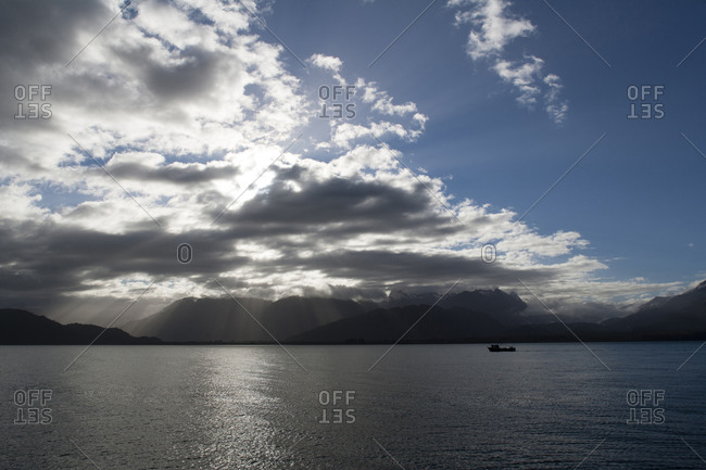 View of sun shinning through clouds over mountains and ocean with fishing boat in the distance