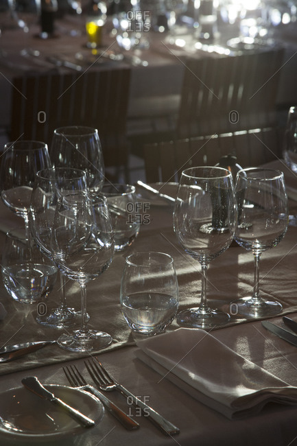 Empty wine and water glasses around place setting at dinner table