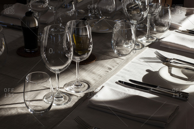 Empty wine and water glasses around place setting at dinner table with strong light