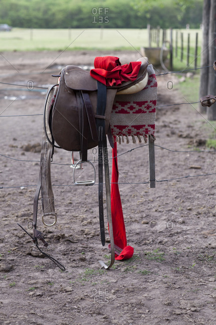 Still-life of polo saddle, red polo wrap resting on wire fence
