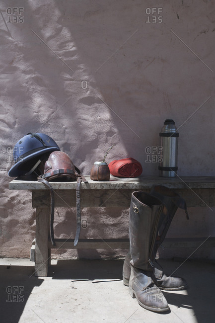 Still-life of polo helmet, boots, and other gear on wooden bench