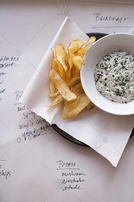 Dish of potato chips and dip over menu items written on paper