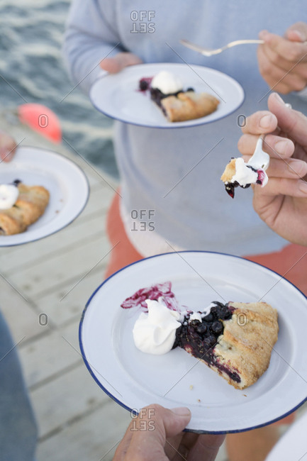 Three people holding plates of blueberry pie on dock