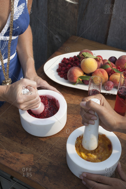 Two women using pestle and mortar to crush fruit to make Bellini cocktails.