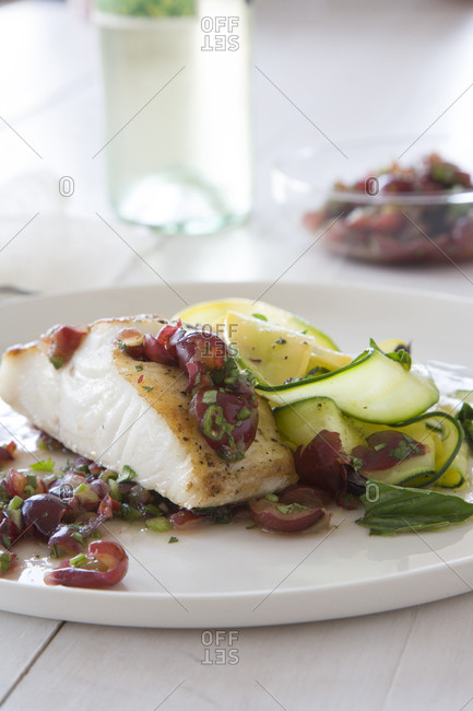 Fish with grapes and sliced cucumber and zucchini side dish.