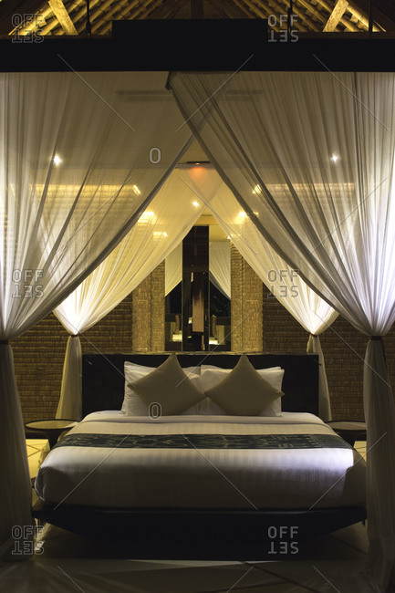 Bed with drawn mosquito net in a villa suite at a resort