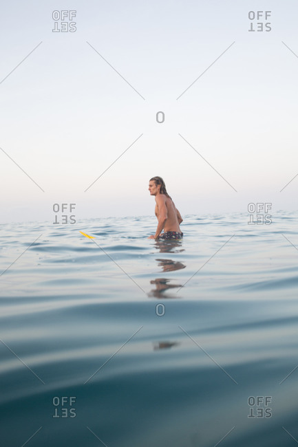 Man waiting for waves to surf while sitting on his surfboard