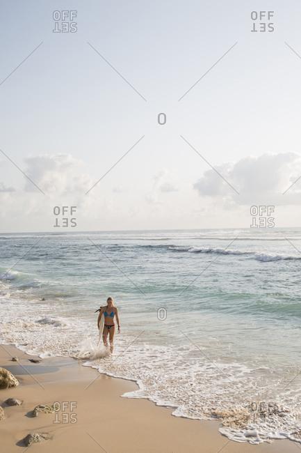 Woman holding surfboard walking on the beach