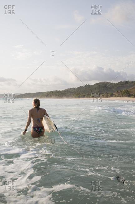 Woman in bikini holding surfboard wading into the water