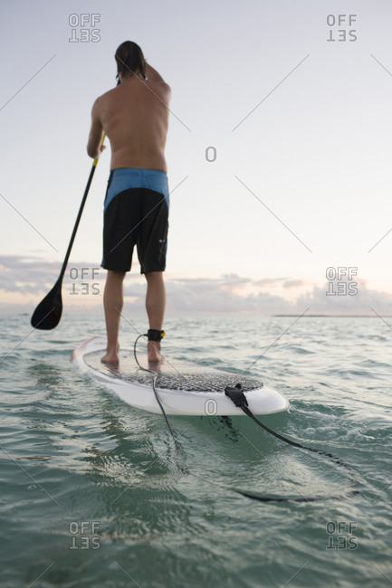 Man paddling away on a paddleboard in the ocean