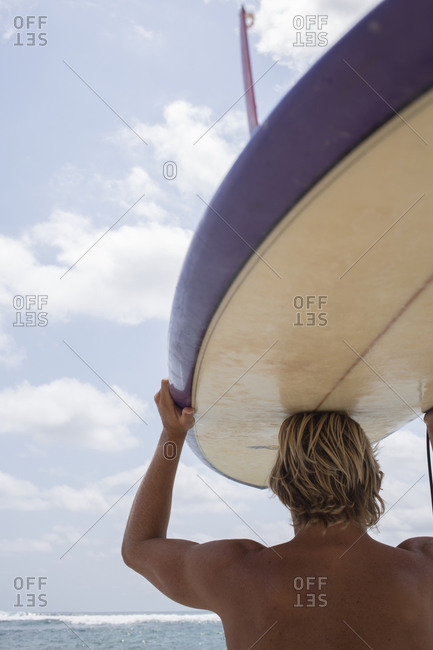 Man with surfboard over his head looking out at the ocean