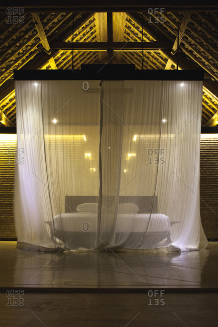 Bed with mosquito net down in a villa at a resort