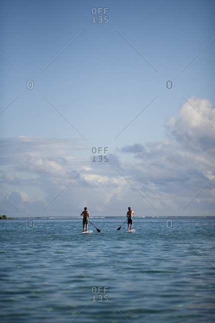 Two men paddle boarding on the ocean