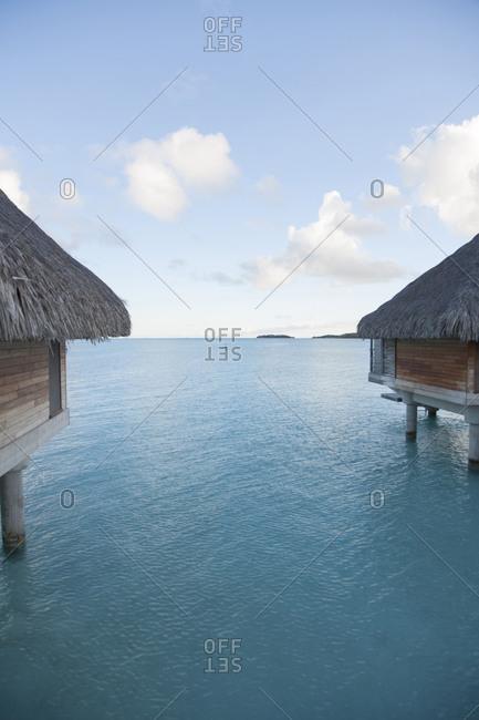 View of calm ocean between overwater bungalows