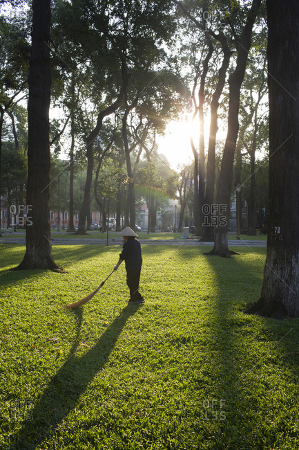 Woman sweeping grass in park
