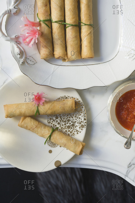 Fried spring rolls on plates with dipping sauce
